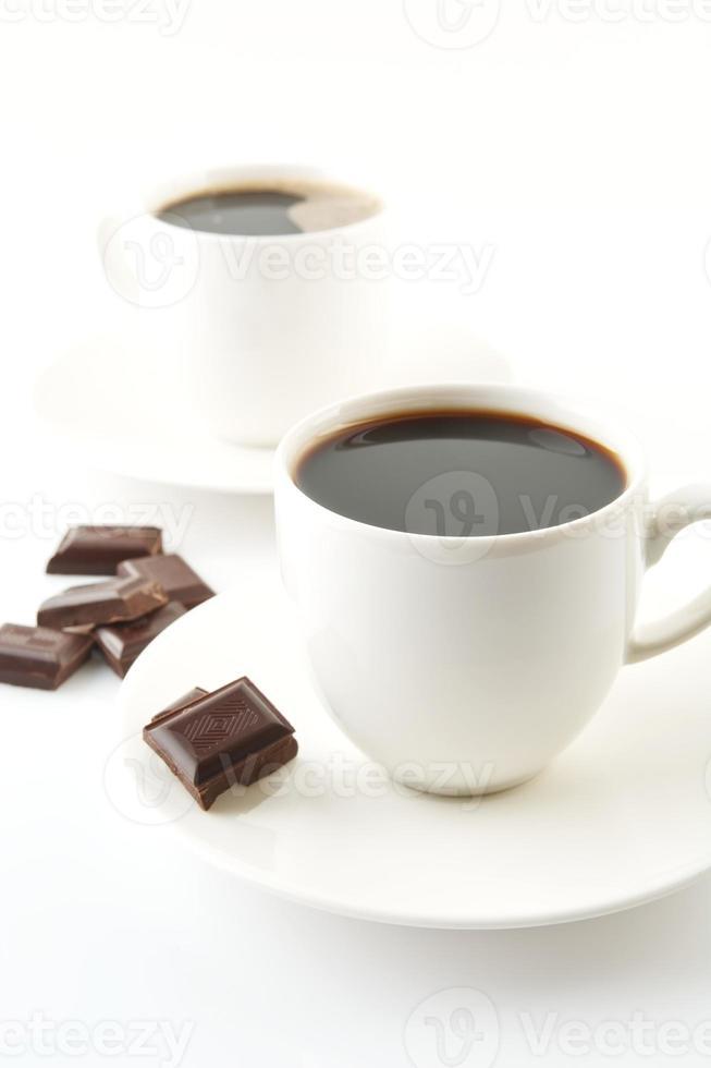 tazze di caffè con cioccolato e piattini su bianco foto