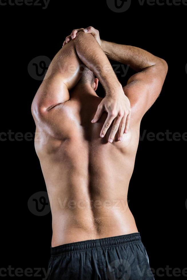 uomo senza camicia che allunga gomito foto