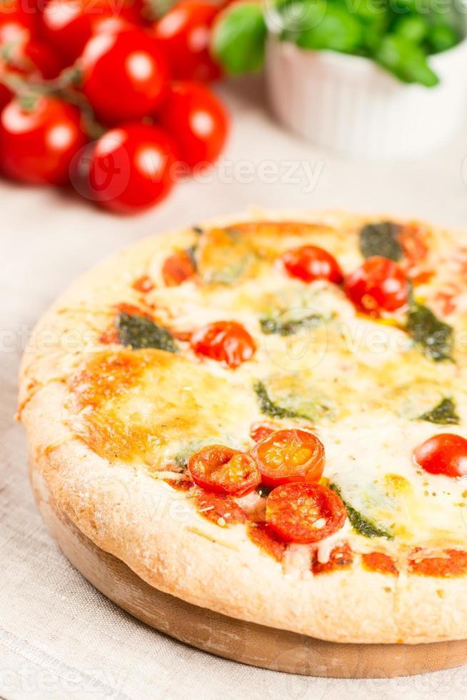 pizza fatta in casa su tavola di legno con pomodori sullo sfondo foto