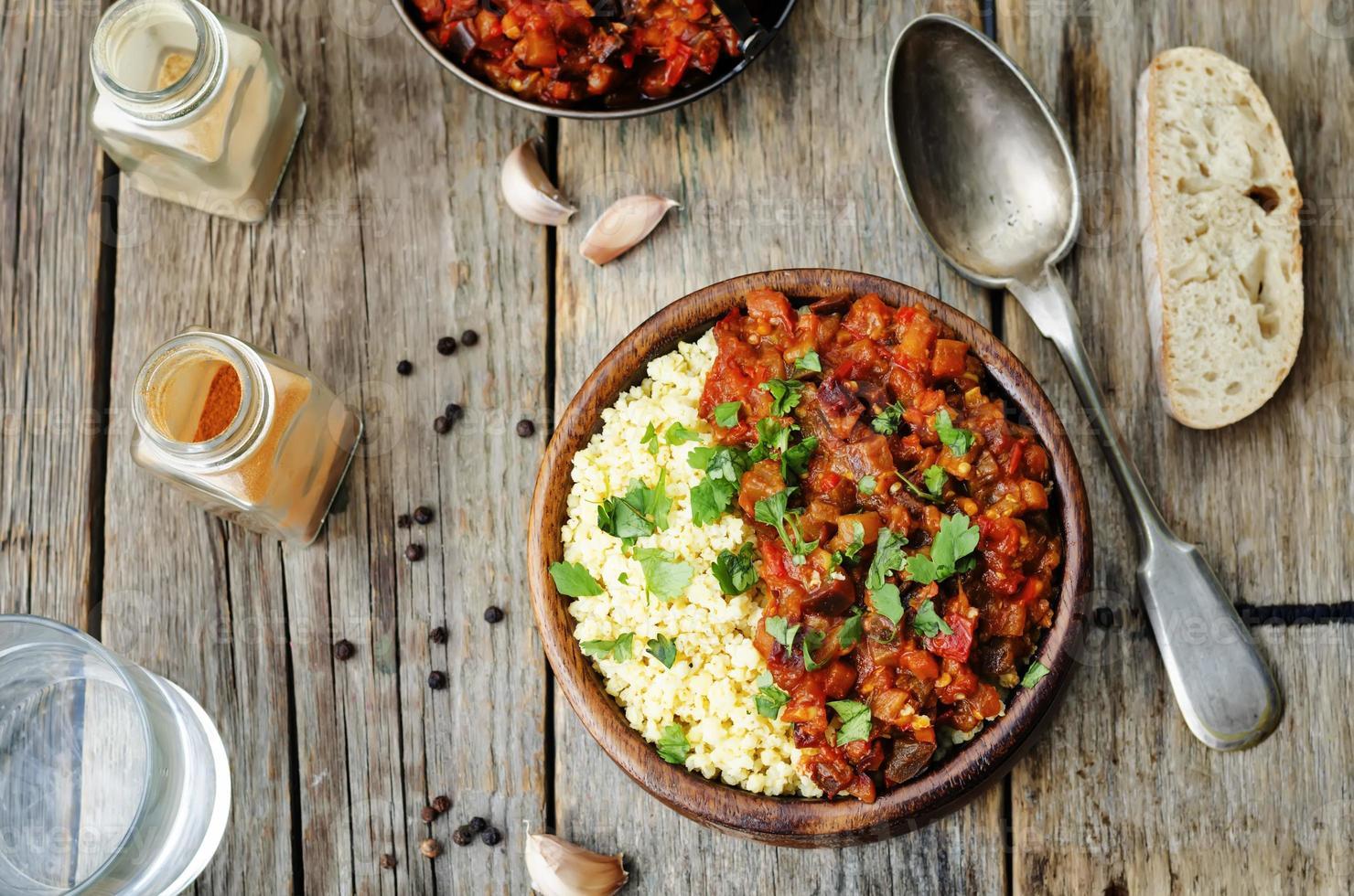 miglio imburrato con curry di melanzane al pomodoro foto