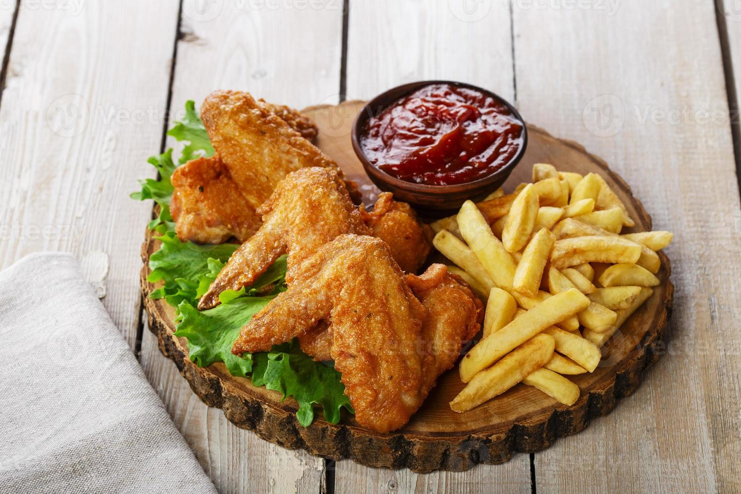 ali di pollo fritto con salsa e patatine fritte foto