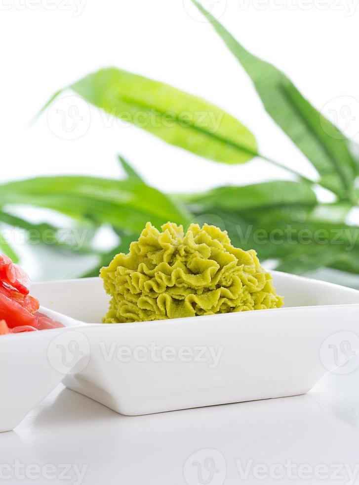 zenzero e wasabi in zolla bianca con la lista di bambù foto