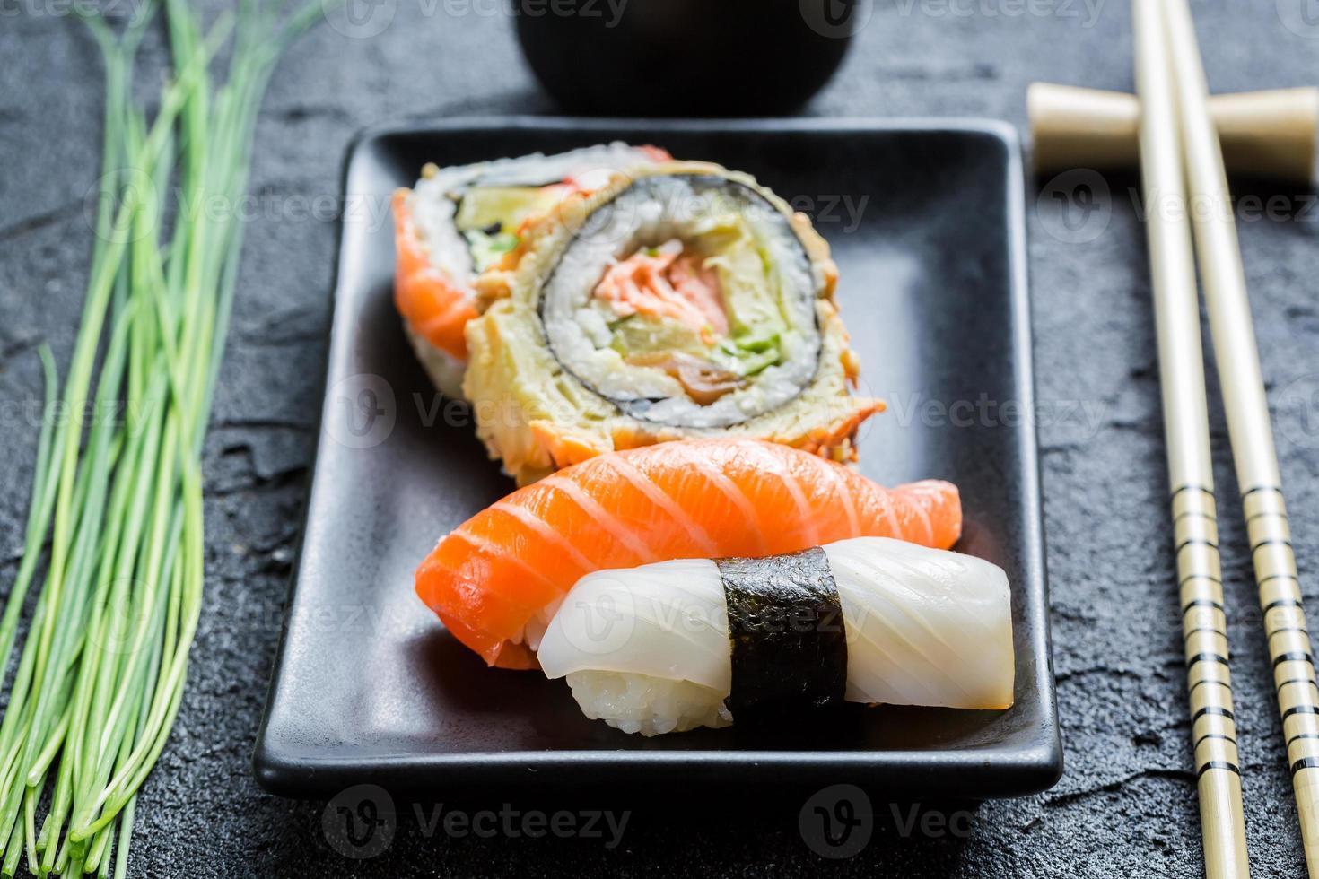 primo piano di sushi fresco, ceramica scura e bacchette foto