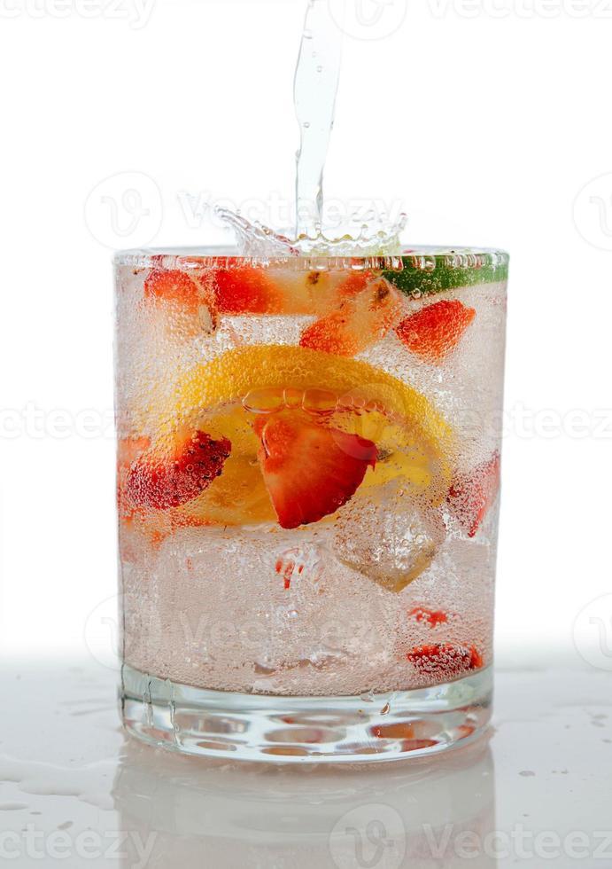 bevanda seltzer con frutta fresca tagliata galleggiante all'interno foto