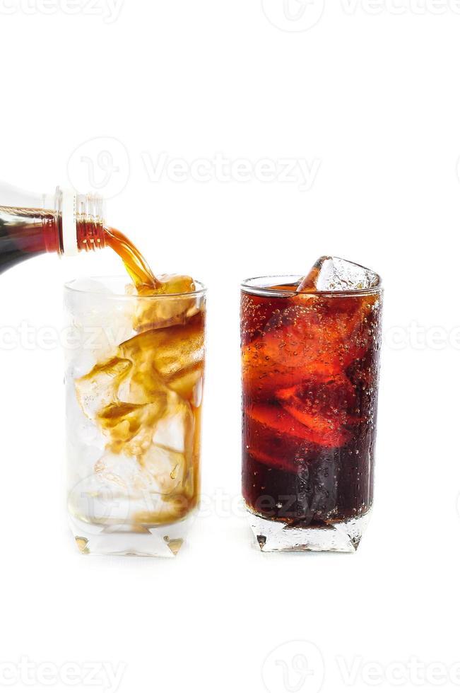 bevanda di cola di versamento da una bottiglia in vetro su bianco foto