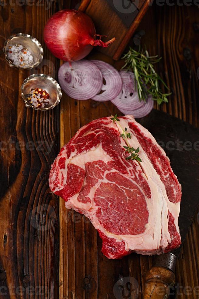 bistecca di ribeye di manzo crudo sul tavolo di legno foto