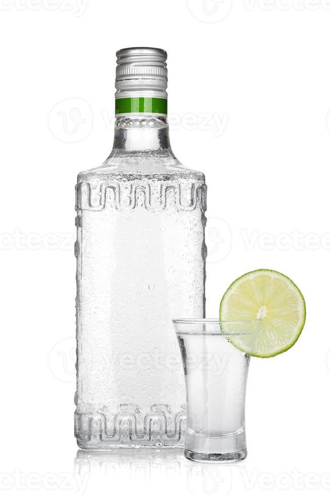 bottiglia di tequila argento e colpo con fetta di lime foto
