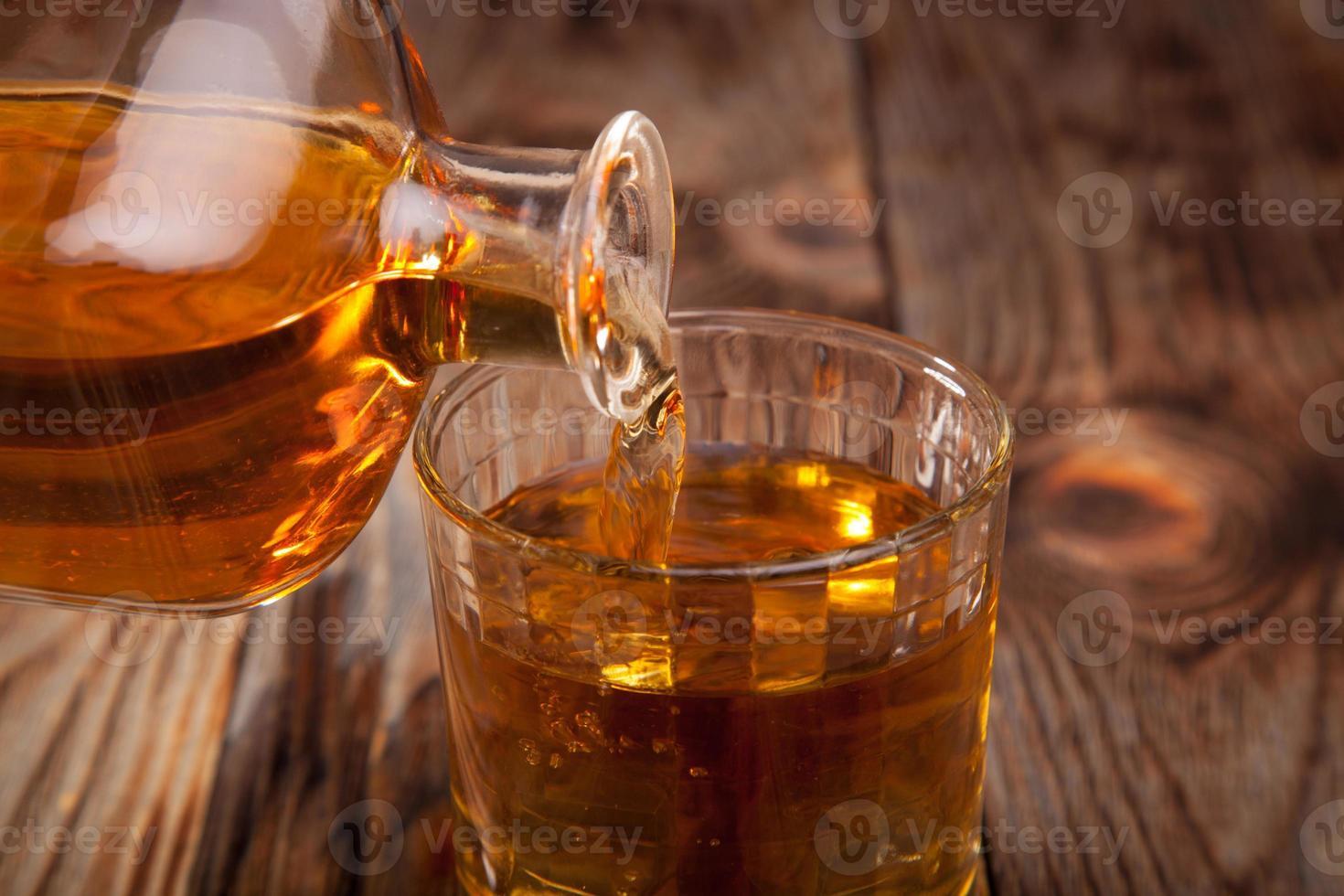 bottiglia di whisky e un bicchiere foto