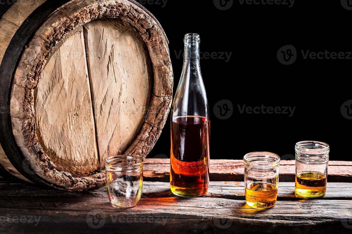 tre bicchieri di whisky invecchiato e una bottiglia foto