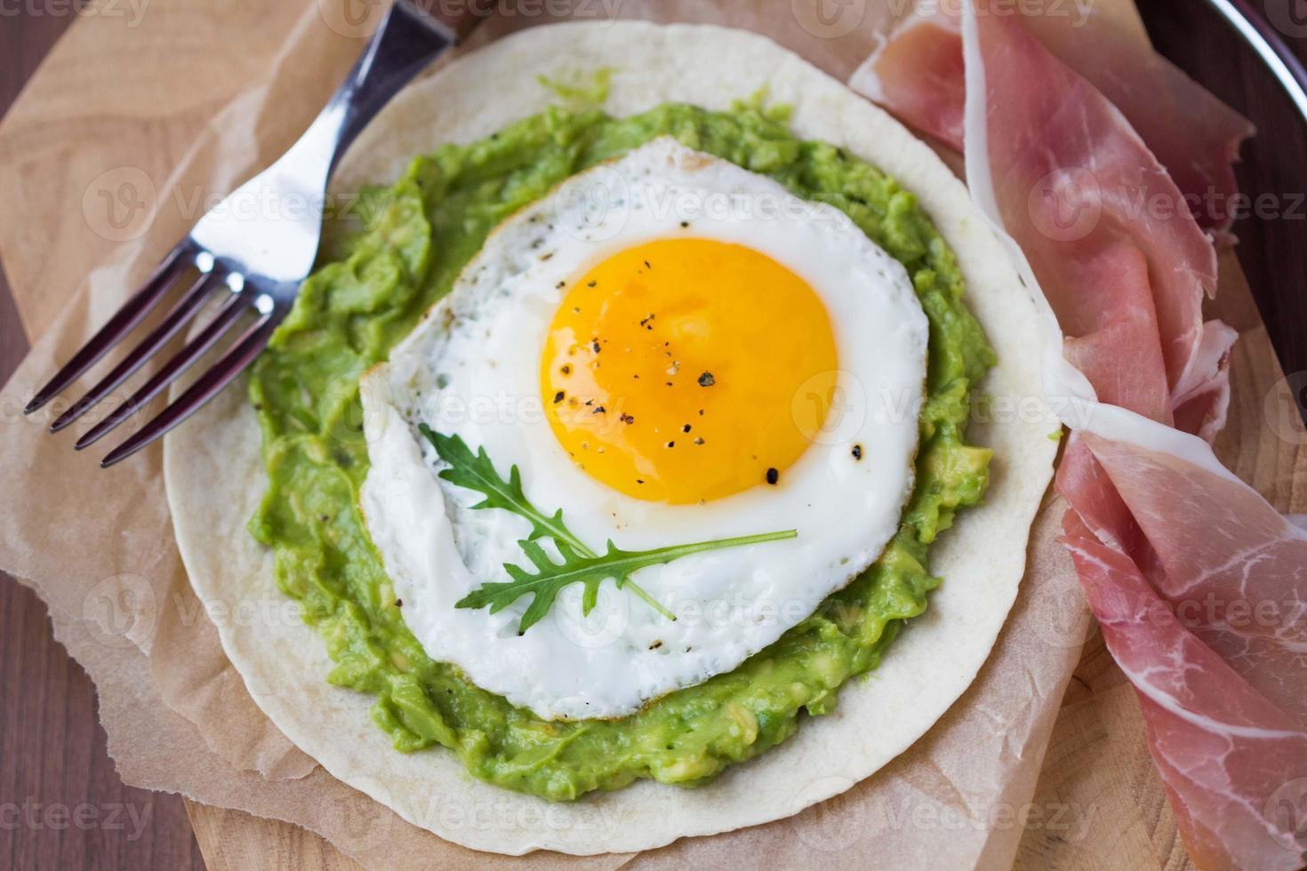 colazione con uovo fritto, salsa di avocado su tortilla di farina foto