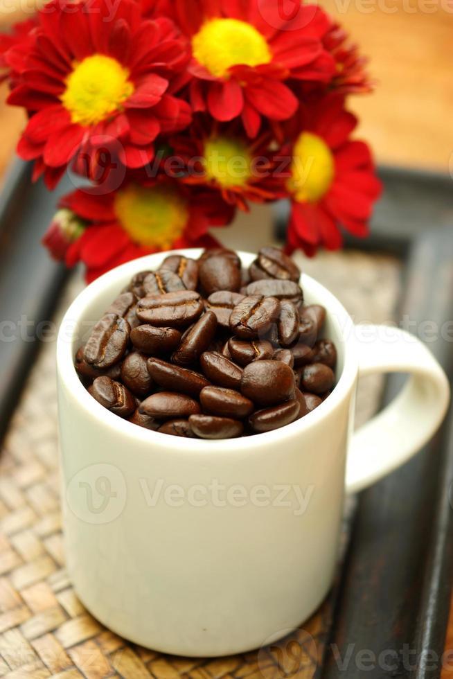 chicco di caffè in tazza sul vassoio di bambù. foto