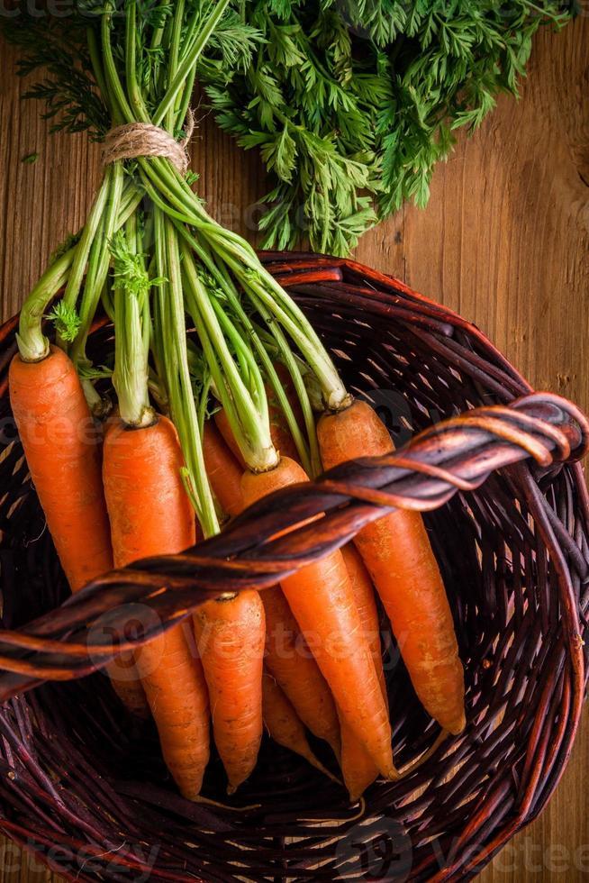 mazzo di carote fresche nel cestino foto