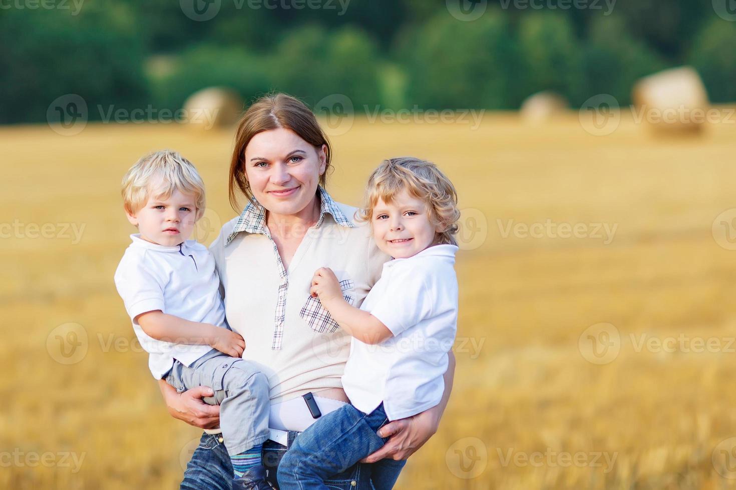 giovane madre e due gemelli ragazzi divertirsi foto