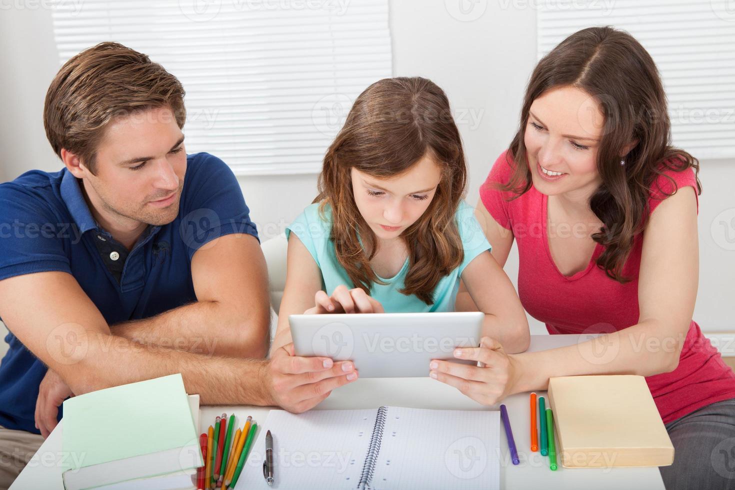 genitori che assistono la figlia nell'uso della tavoletta digitale foto