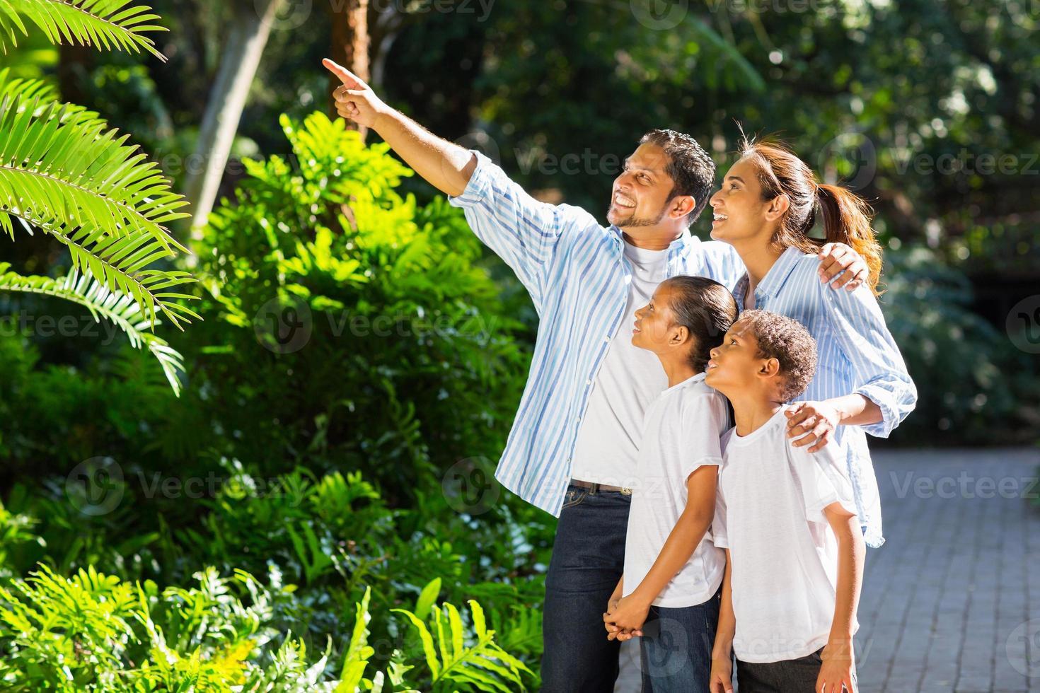 famiglia indiana guardando e indicando nel parco foto