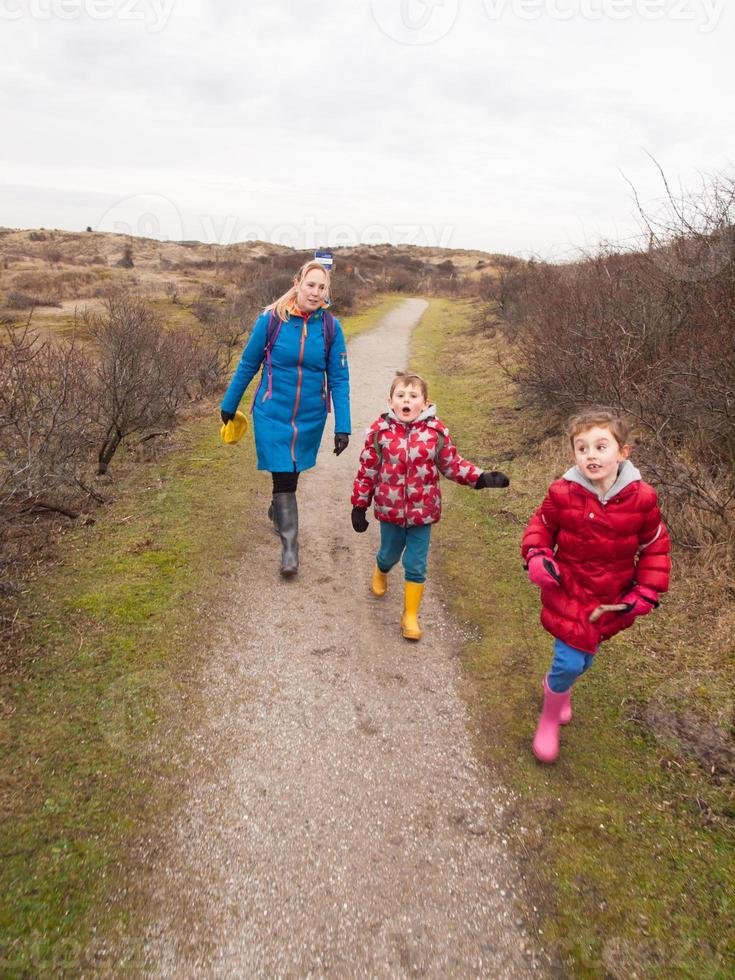 donna e due bambini piccoli che camminano attraverso il paesaggio di dune foto