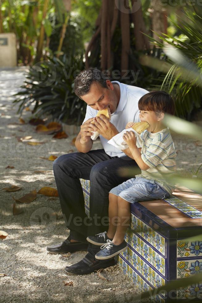 ragazzo che mangia panino con suo padre foto