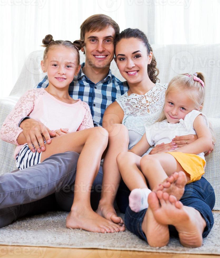 genitori allegri con due figlie foto