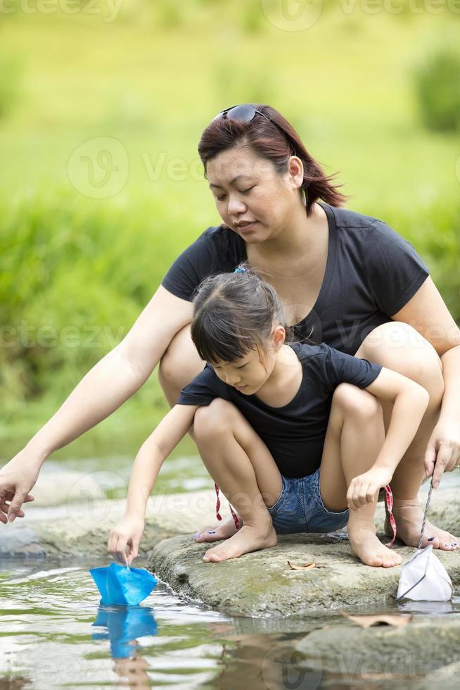 giovane asiatico madre e figlia incollaggio dal fiume foto