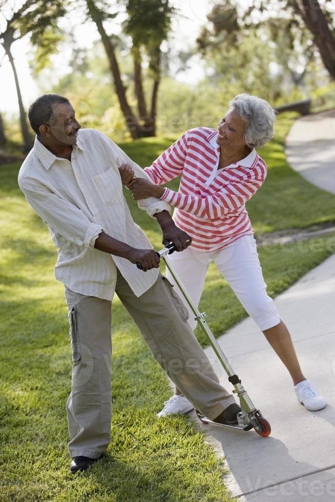 coppia giocando su push scooter nel parco foto