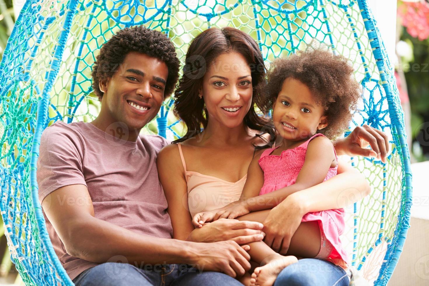 famiglia che si distende sul sedile da altalena da giardino esterno foto