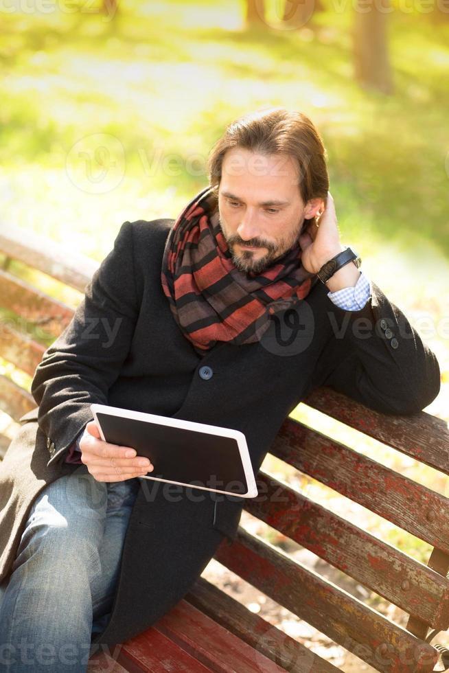 uomo di mezza età appoggiato sulla panchina all'aperto foto