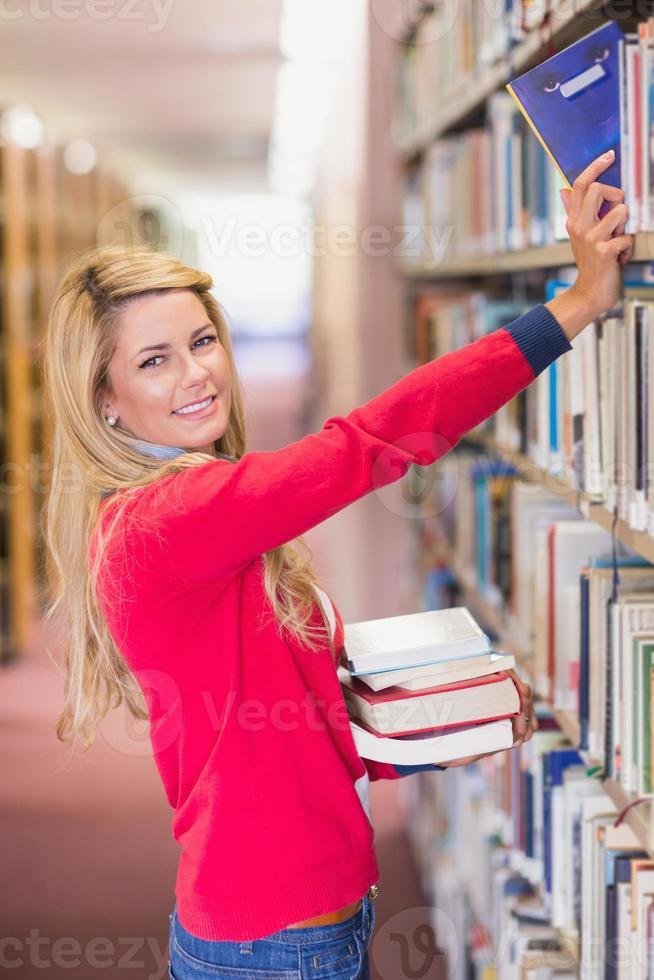 studente maturo raccogliendo il libro in biblioteca foto