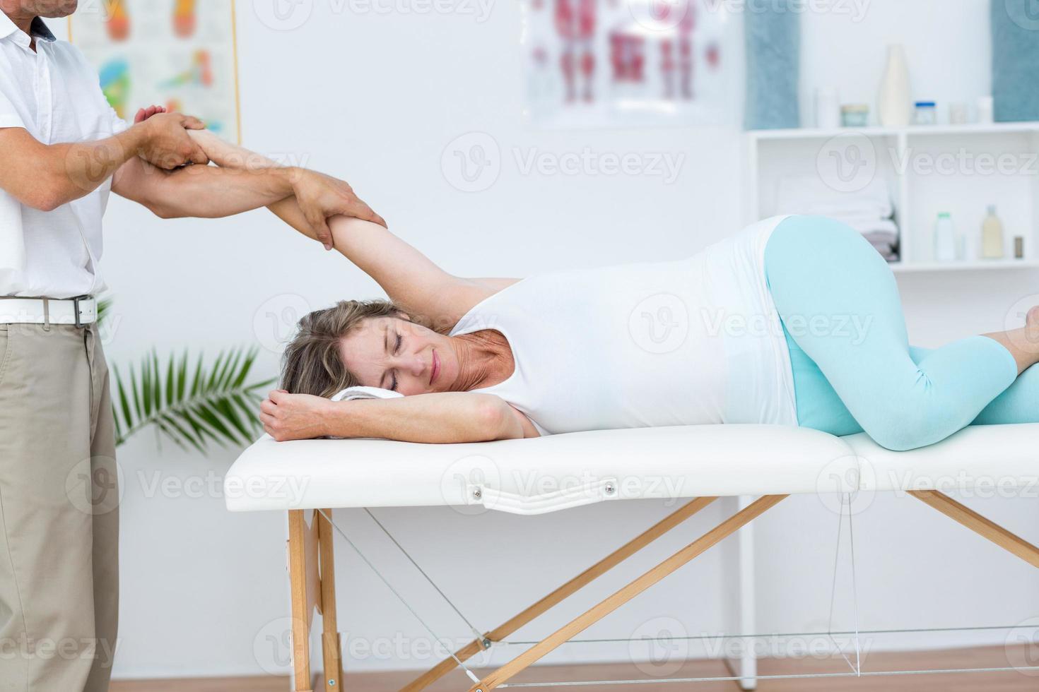 dottore che allunga il braccio dei suoi pazienti foto