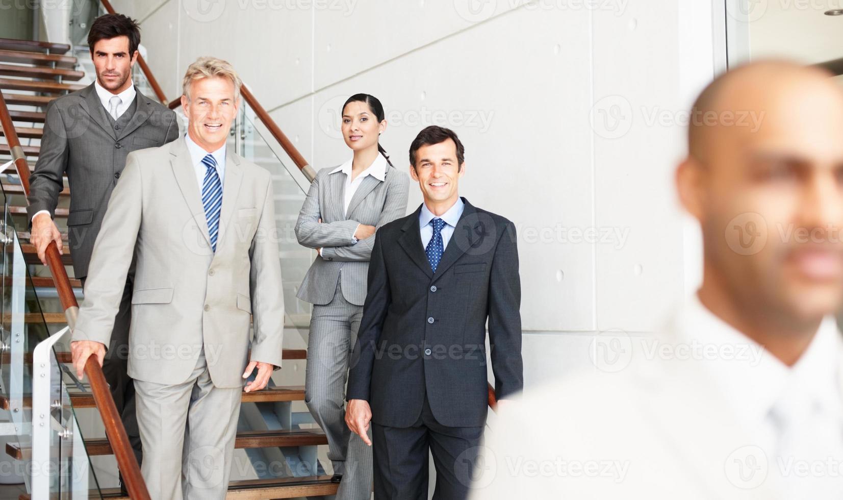 primo piano di uomo d'affari con i colleghi in piedi in background foto