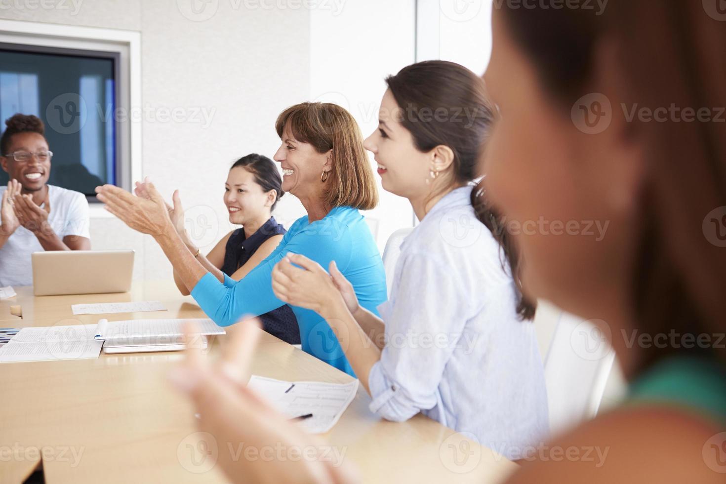 persone di affari che applaudono collega in sala del consiglio foto