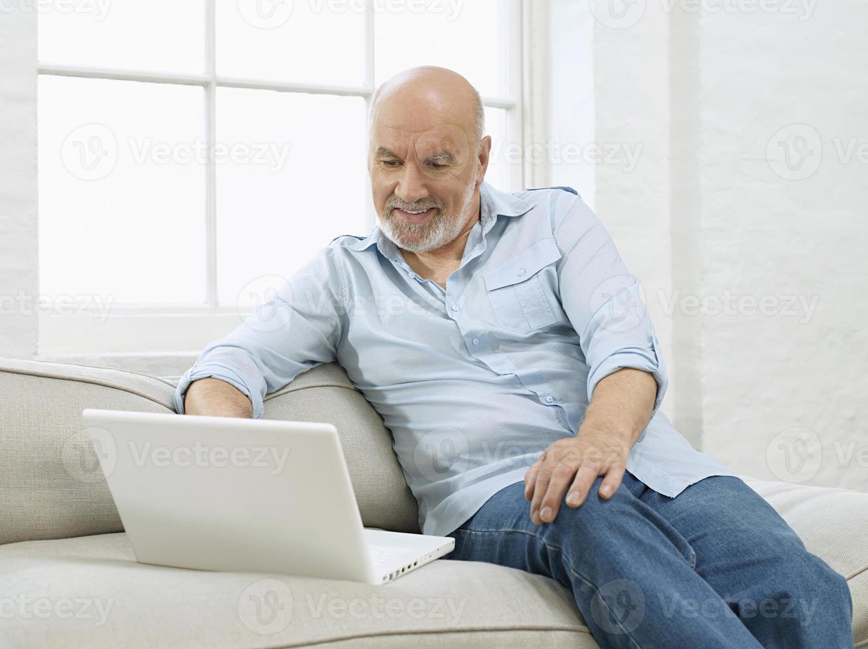 uomo maturo con il portatile sul divano foto