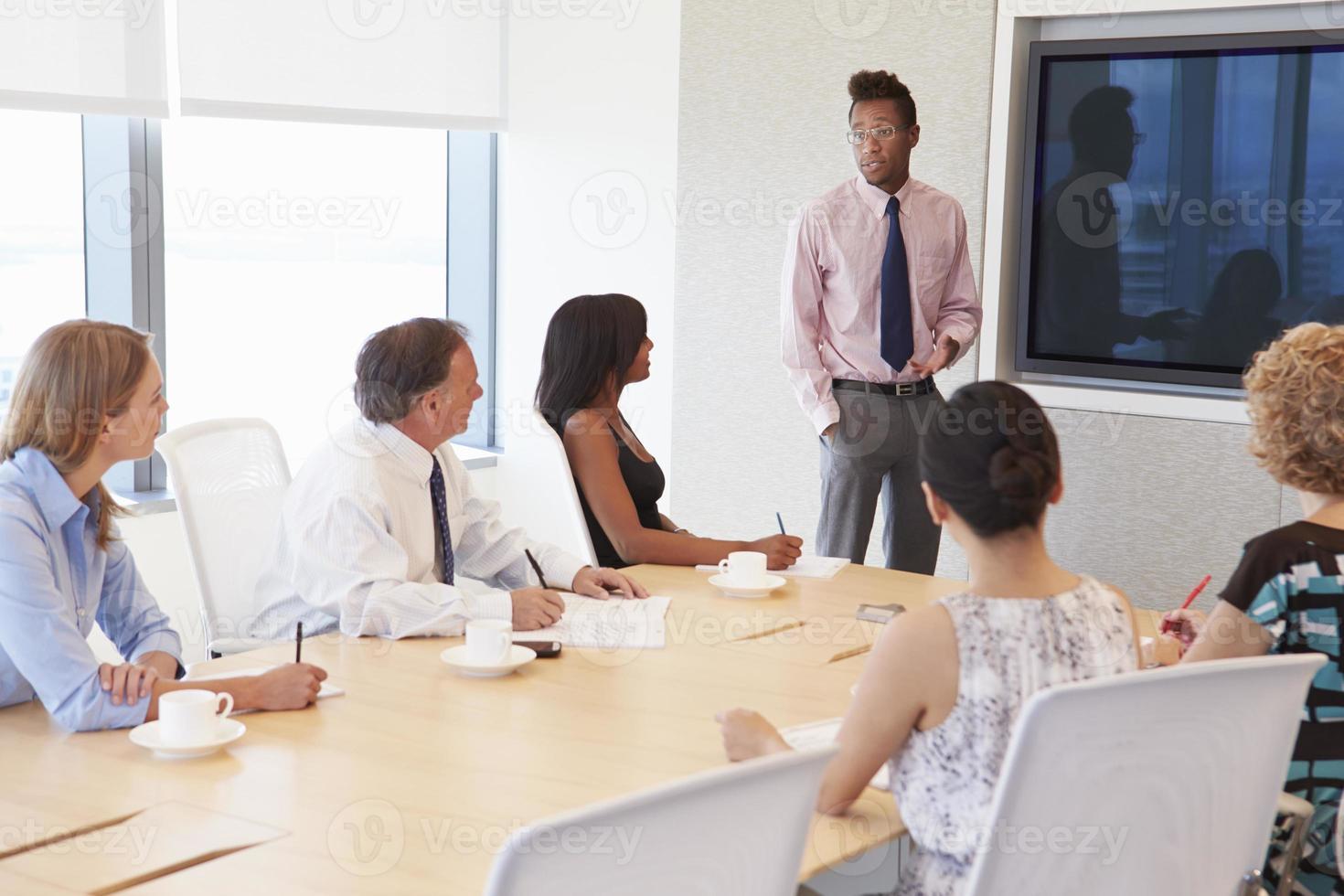 uomo d'affari dallo schermo affrontando la riunione della sala del consiglio foto