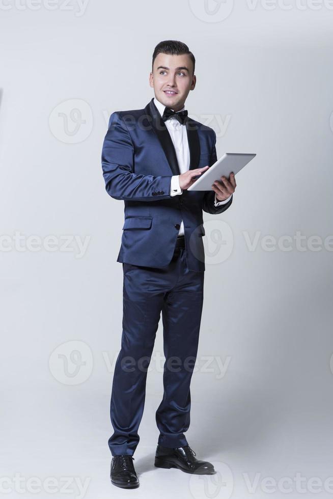 uomo alla moda in un vestito con cravatta a farfalla in piedi foto