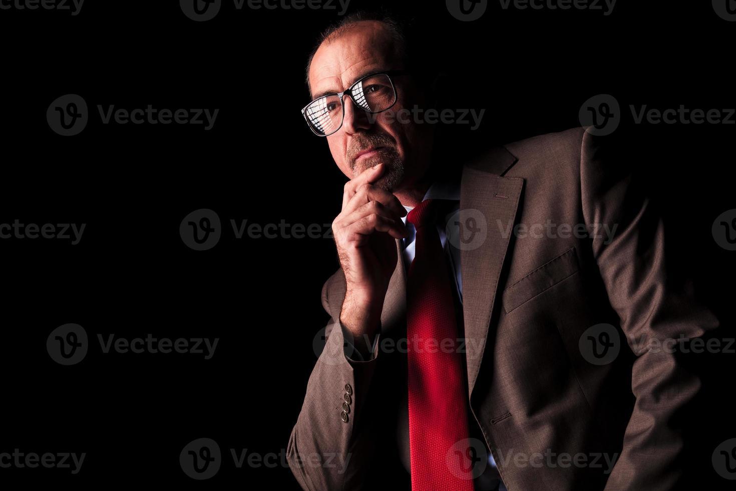 vista laterale di un uomo d'affari senior riflessivo guardando lontano foto
