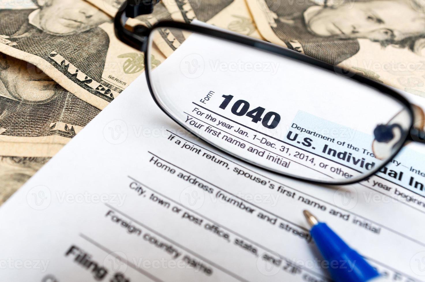 Modulo di dichiarazione dei redditi individuale 1040 attraverso occhiali e contanti foto