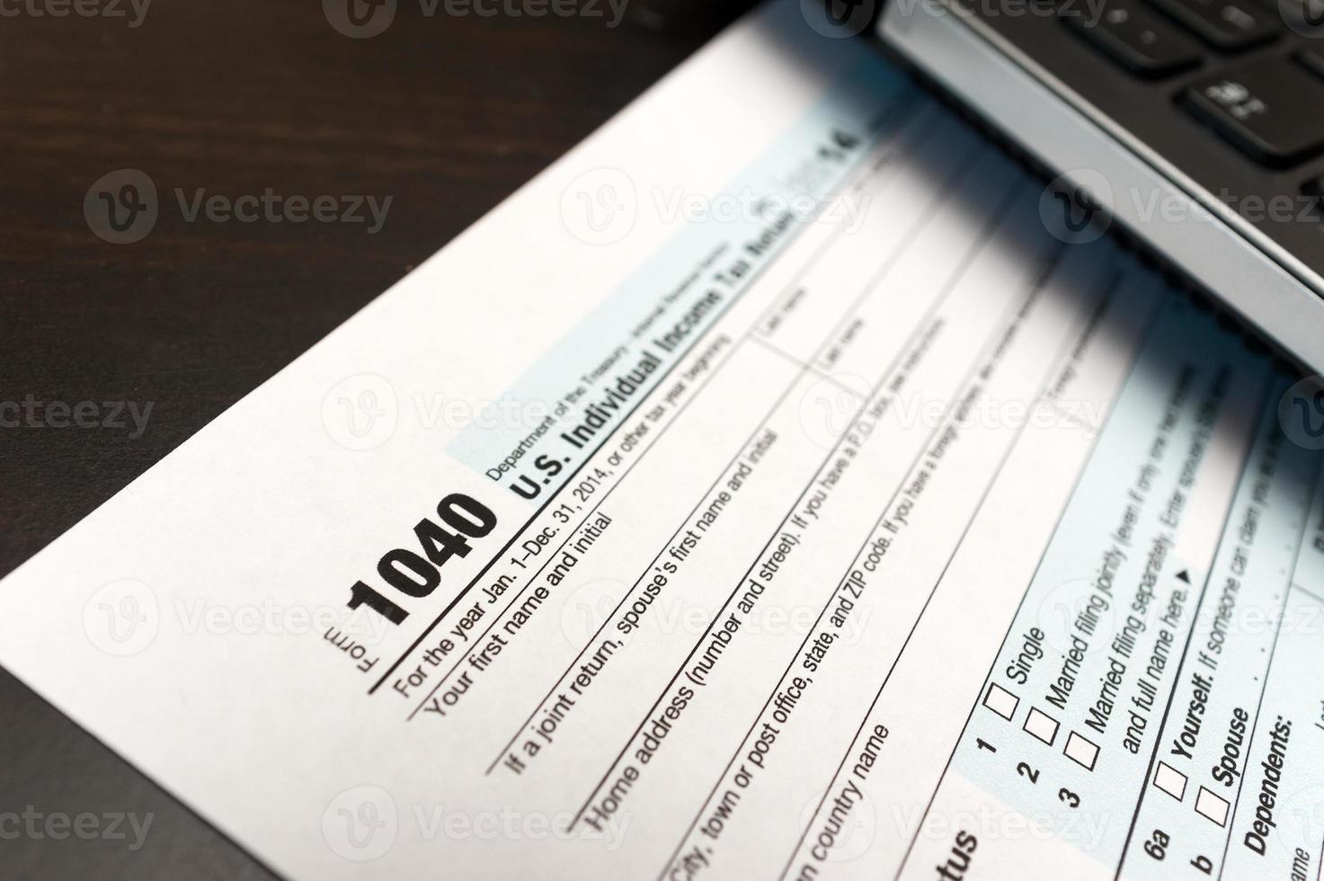 Primo piano del modulo di dichiarazione dei redditi individuale 1040 con il computer portatile foto