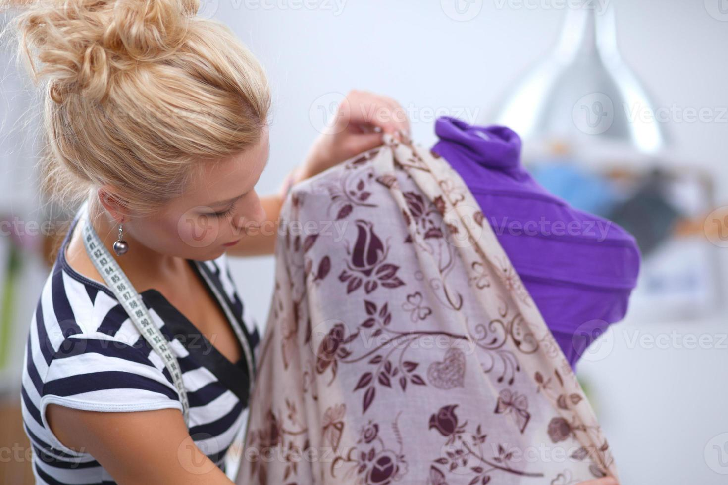 stilista sorridente che ripara vestito sul manichino in uno studio foto