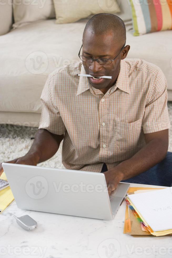 uomo con la penna in bocca al computer portatile, vista elevata foto