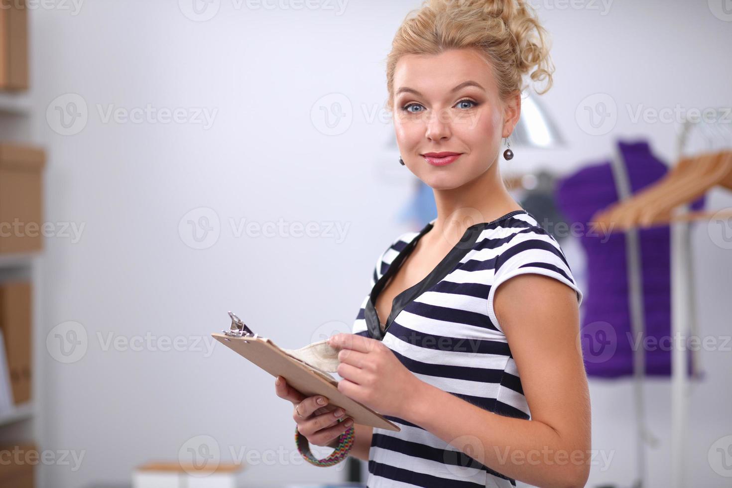 stilista sorridente in piedi vicino al manichino in ufficio foto