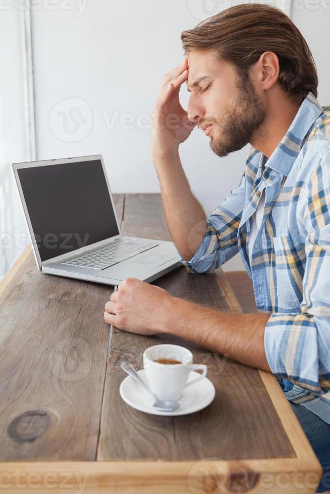 uomo casuale che per mezzo del computer portatile che mangia caffè foto