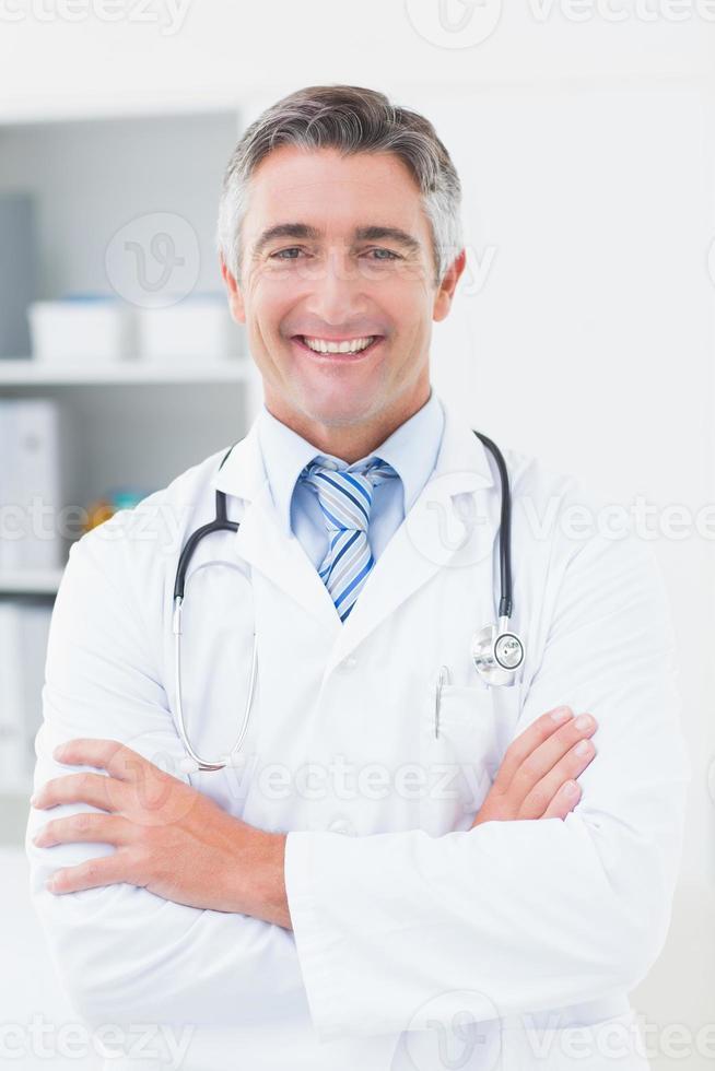 medico fiducioso con le braccia incrociate in clinica foto