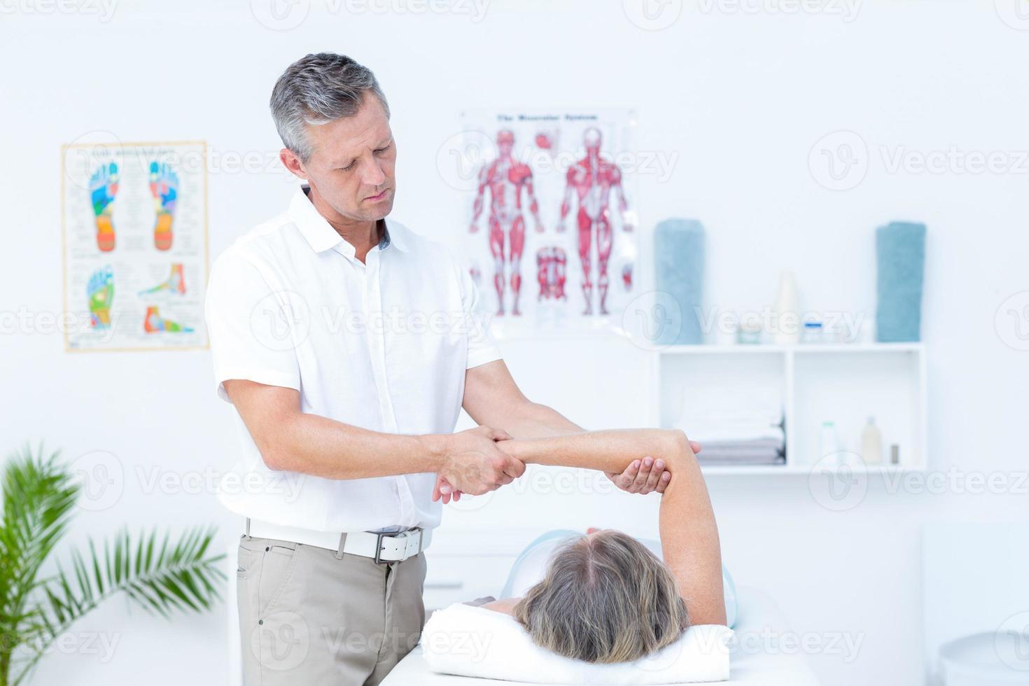 Fisioterapista che esamina il braccio dei suoi pazienti foto