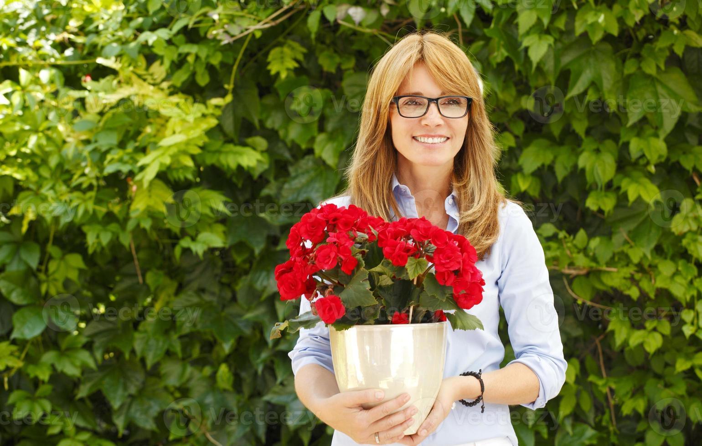 donna di mezza età con vaso di fiori foto