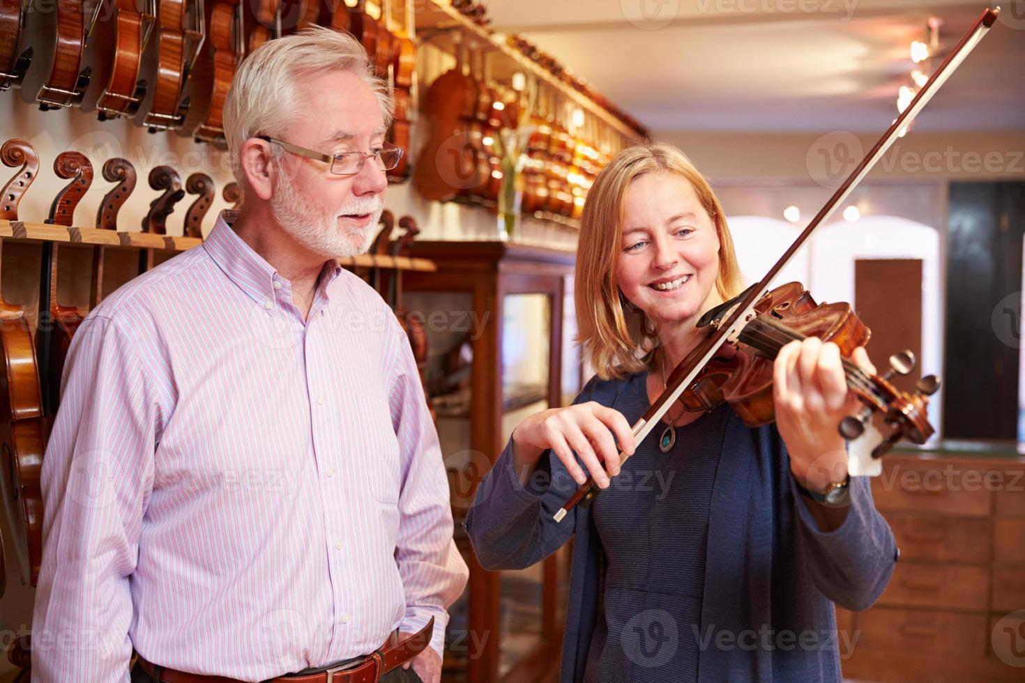cliente che prova violino nel negozio di musica foto