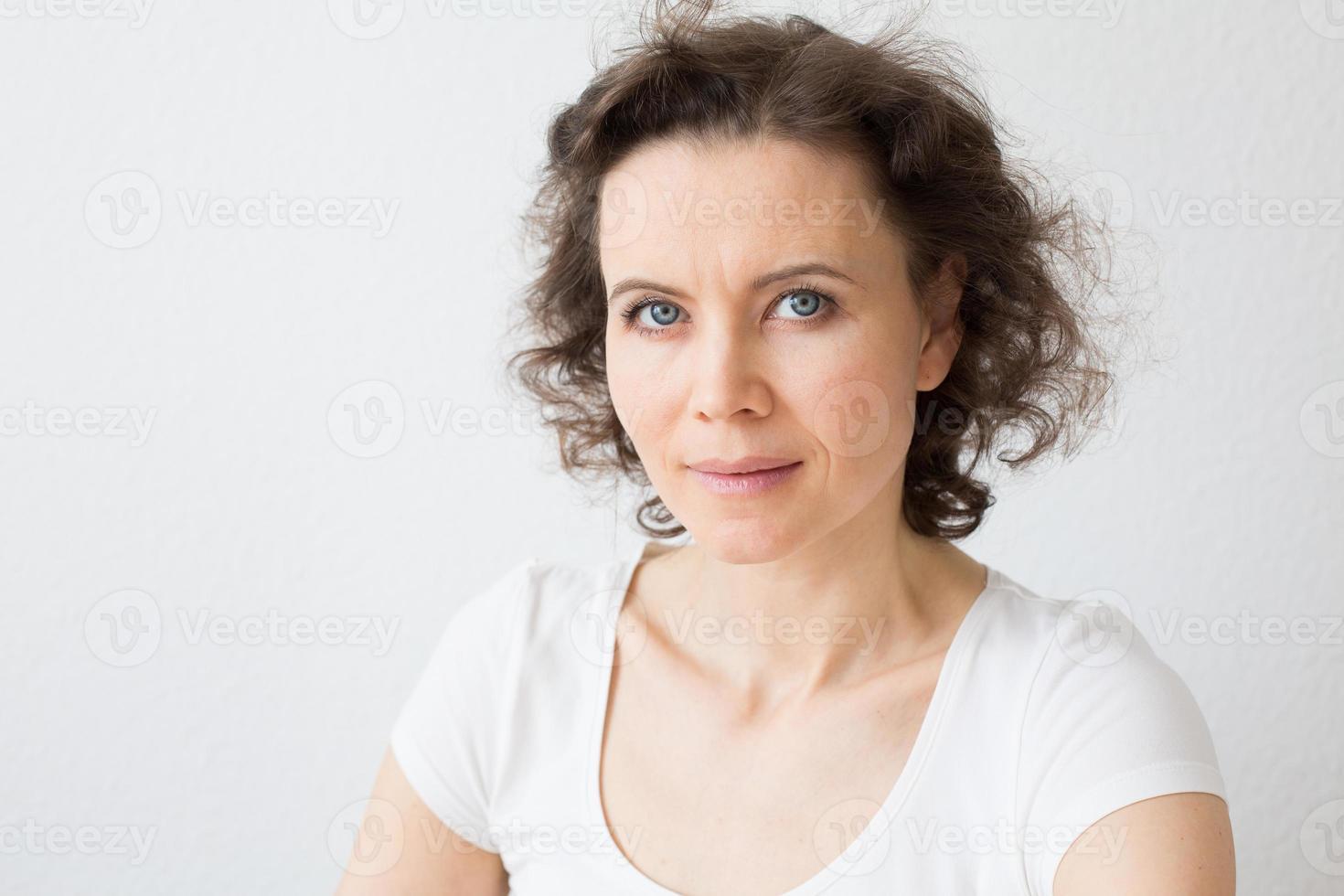donna dai capelli castani, sguardo attento alla telecamera foto