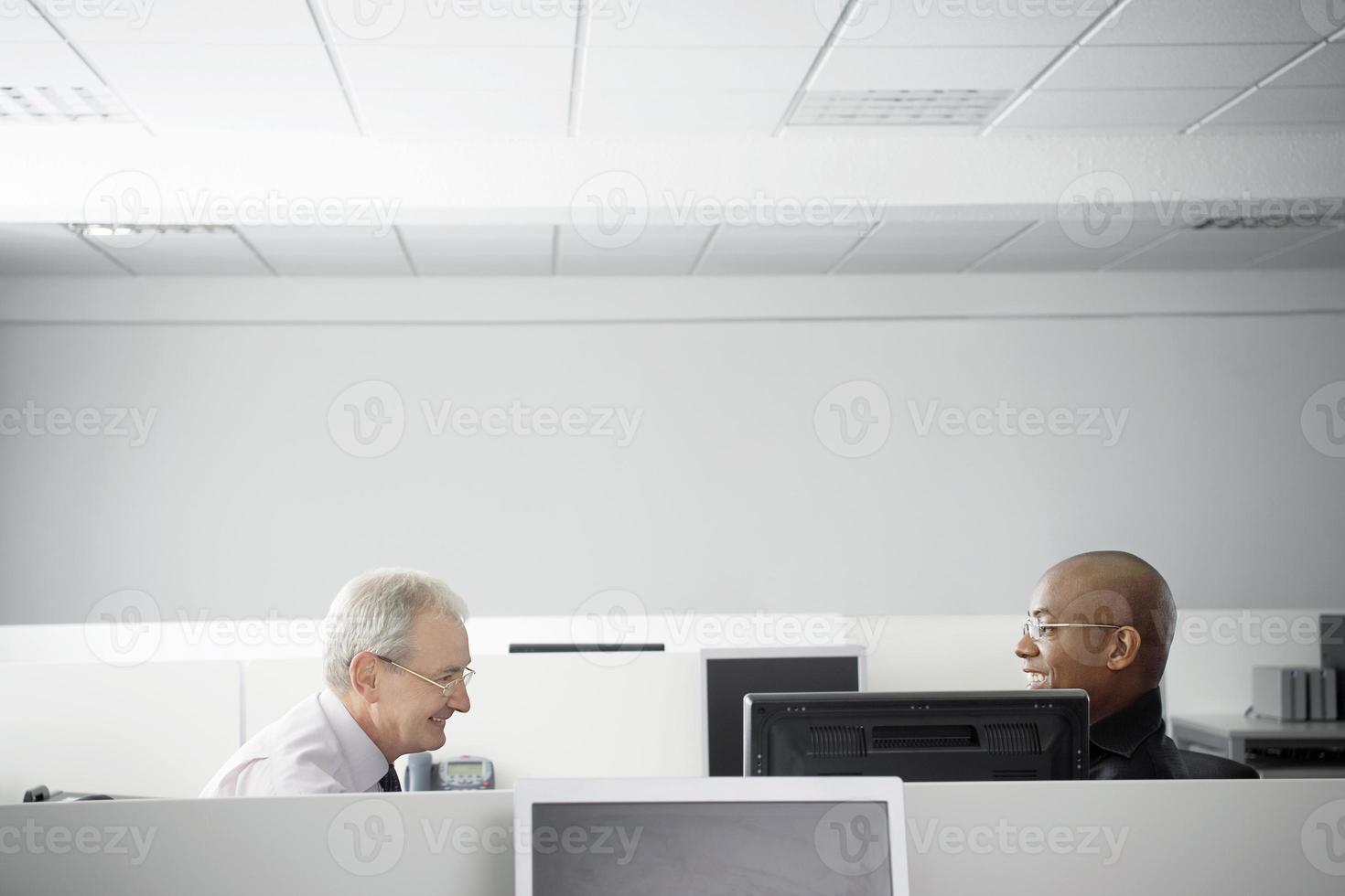 uomini d'affari avendo incontro nel cubicolo di ufficio foto