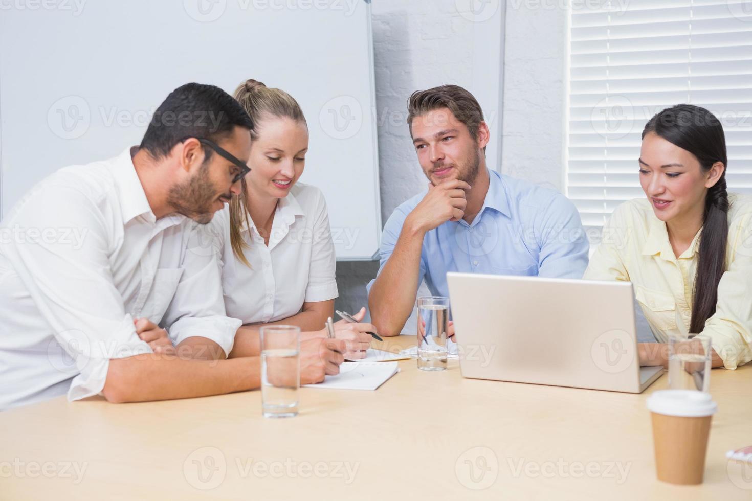 squadra di affari casuali che ha una riunione utilizzando il computer portatile foto