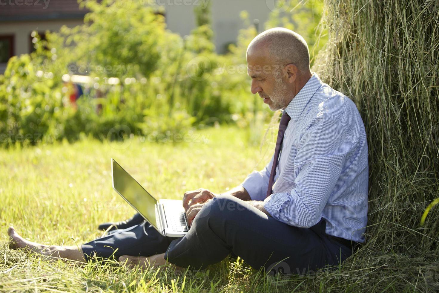 Germania, Baviera, uomo d'affari che lavora con il computer portatile all'aperto foto