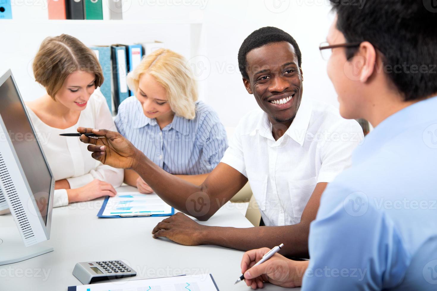 felici uomini d'affari riuniti intorno al computer portatile foto