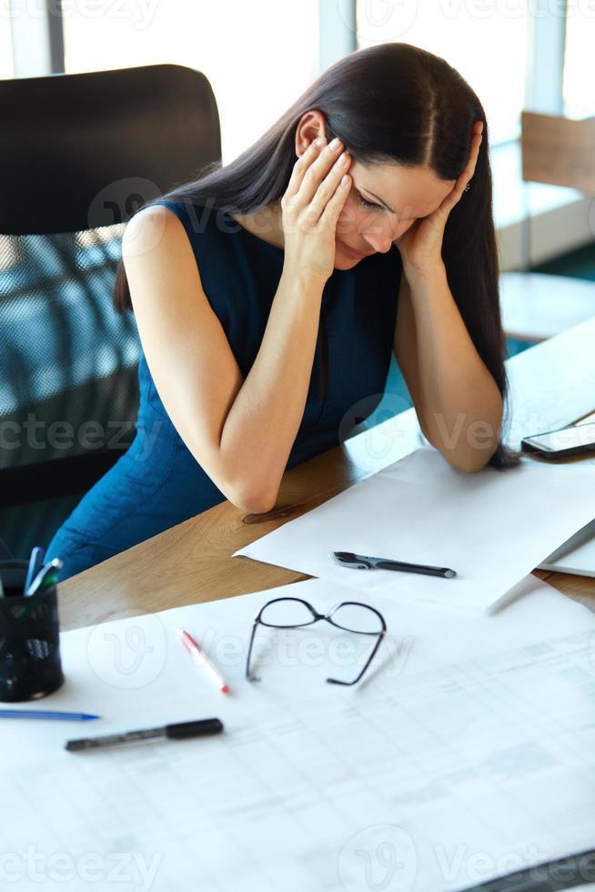 donna d'affari stressata al suo posto di lavoro. uomini d'affari foto